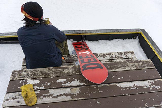Snowboarder sitting next to the DC Supernatant